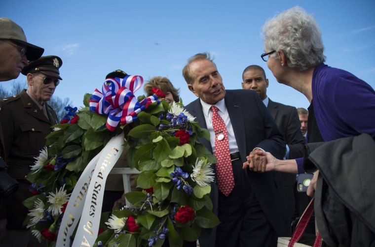 Senator and World War II veteran Bob Dole (3rd R) talks with visitors and fellow WWII Veterans after laying a wreath at the World War II Memorial on Veteran's Day in Washington, DC, November 11, 2015. (AFP Photo/Jim Watson)