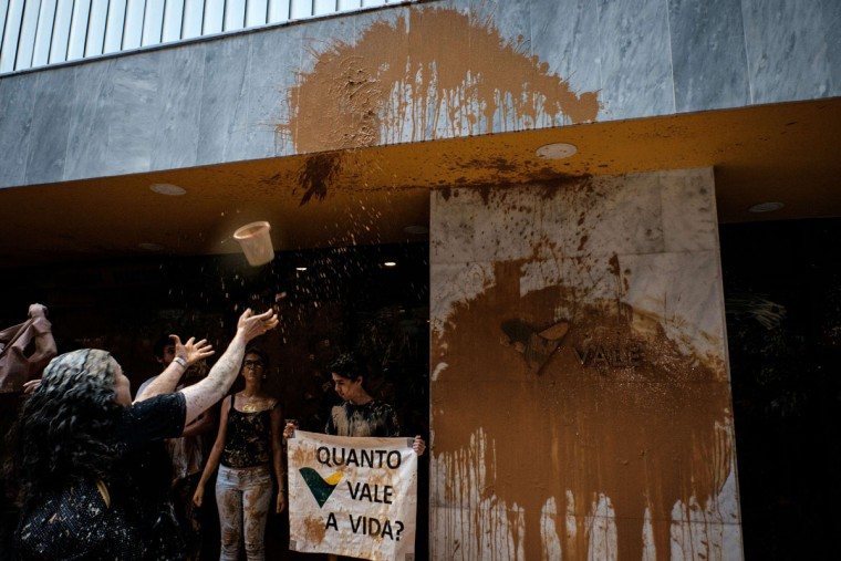"A protester throws muddy water on the façade of Brazilian mining company Vale headquarters as another holds a sign reading ""How much does a life cost?"" in Rio de Janeiro, Brazil, on November 16, 2015. The bursting of two dams at a mine operated by Brazilian company Samarco - equally owned by Vale and Australian BHP Billiton- unleashed torrents of waste that flattened a village in Minas Gerais State on November 5 killing ten people. Brazilian mining firm Samarco promised Monday to pay at least $260 million for damage from the bursting, prosecutors said. (YASUYOSHI CHIBA/AFP/Getty Images)"