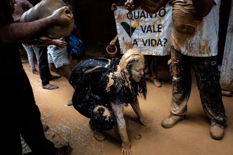 "Protesters throw muddy water on the façade of Brazilian mining company Vale headquarters next to a sign reading ""How much does a life cost?"" in Rio de Janeiro, Brazil, on November 16, 2015. The bursting of two dams at a mine operated by Brazilian company Samarco - equally owned by Vale and Australian BHP Billiton- unleashed torrents of waste that flattened a village in Minas Gerais State on November 5 killing ten people. Brazilian mining firm Samarco promised Monday to pay at least $260 million for damage from the bursting, prosecutors said. (YASUYOSHI CHIBA/AFP/Getty Images)"