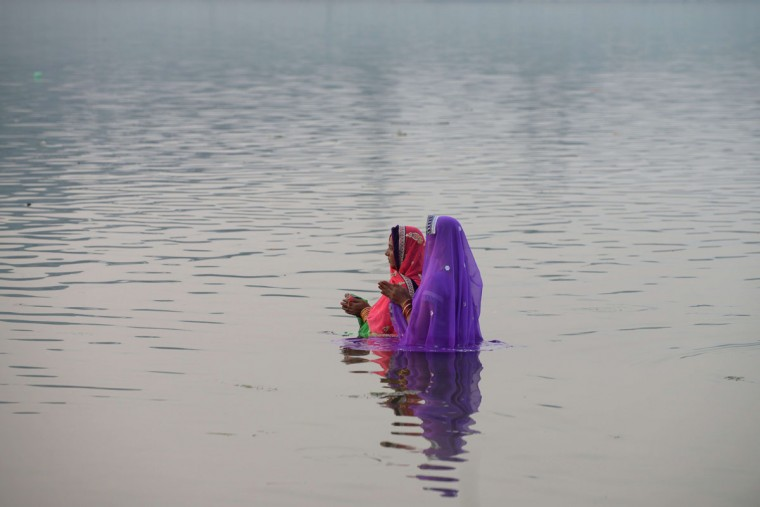 Indian Hindu devotees offer prayers during the Chhat festival on the banks of the river Sabarmati in Ahmedabad on November 17, 2015. Chhath festival, also known as Surya Pooja (worship of the sun), is observed in eastern parts of India where homage is paid to the sun and water Gods eight days after Diwali, the festival of lights. During Chhath festival, devotees undergo a fast and offer water and milk to the Sun God at dawn and dusk. (AFP Photo/P / )