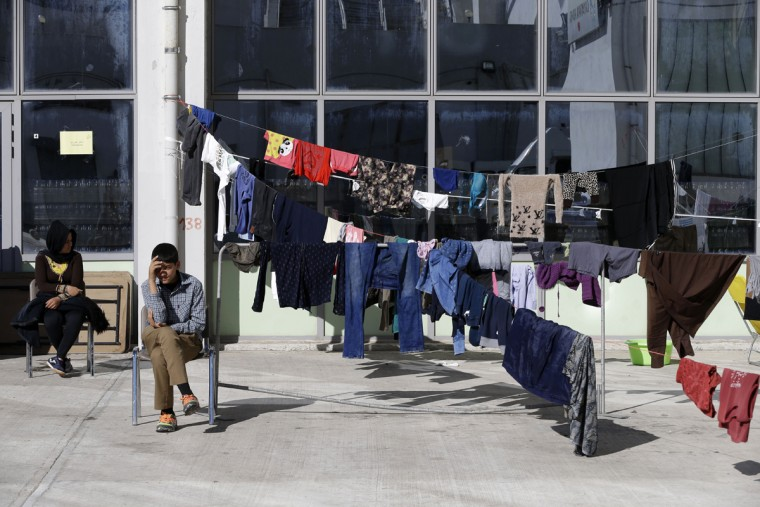 Afghan migrants sit next to laundry at the Galatsi Olympic Hall in Athens, Wednesday, Nov. 4, 2015. The disused facility, used during the Athens Olympics 2004, reopened a month ago for migrants as more than 600,000 people have arrived in Greece so far this year trying to head to more prosperous European Union countries in the north. (AP Photo/Thanassis Stavrakis)