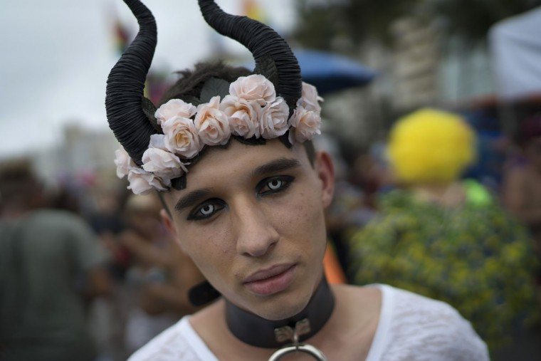 A man wearing special contact lenses poses for a picture during the Gay Pride Parade at Copacabana beach, in Rio de Janeiro, Brazil, Sunday, Nov. 15, 2015. (AP Photo/Leo Correa)