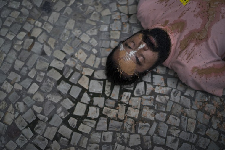 A man lies on the sidewalk during a protest against the Brazilian mining company Vale, in Rio de Janeiro, Brazil, Monday, Nov. 16, 2015. The demonstrators demand that the company take responsibility for the damage caused by two dams that burst at its iron ore mine, that wiped out a village in the southeastern state of Minas Gerais. (AP Photo/Leo Correa)