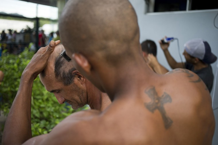 "Cuban migrants set up a makeshift barber shop outside the immigration office in the bordertown PeÒas Blancas, Costa Rica, Tuesday, Nov. 17, 2015. Costa Rican Foreign Minister Manuel Gonzalez said in a radio interview Tuesday that there are nearly 2,000 people currently at the border being blocked by Nicaraguan soldiers from entering the country. He proposed the creation of a ""humanitarian corridor"" for Cubans transiting Central America. (AP Photo/Esteban Felix)"