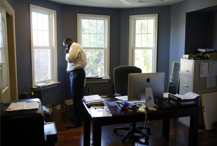 "In this Oct. 16, 2015 picture, funeral director John Williams makes a phone call from his office in Baltimore. ""You can't be soft in the hood,"" Williams said. ""You can't be soft as an undertaker either."" (AP Photo/Patrick Semansky)"