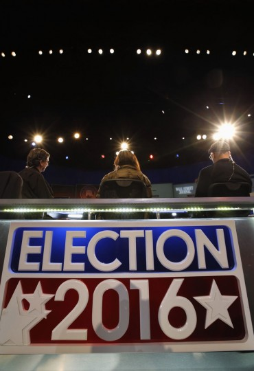 Workers sit in for the moderators in preparation for Tuesday's Republican debate, Monday, Nov. 9, 2015, in Milwaukee. (AP Photo/Morry Gash)