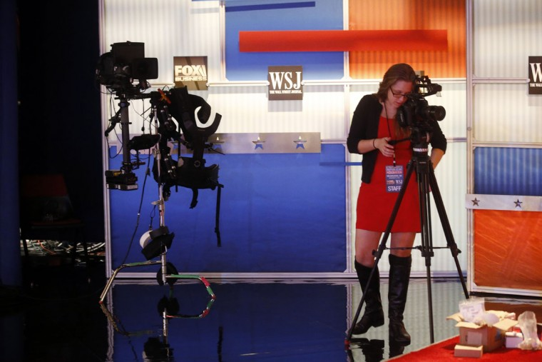 A woman video tapes behind the stage Monday, Nov. 9, 2015, in preparation of for Tuesday's Republican debate in Milwaukee. (AP Photo/Morry Gash)