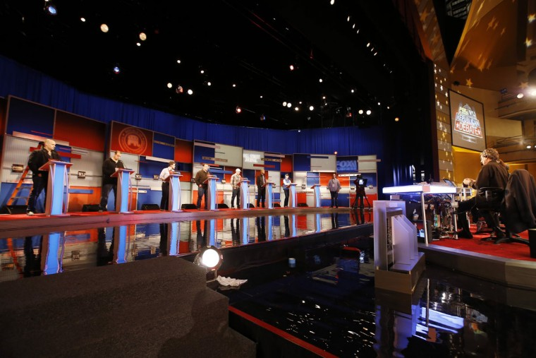 Workers stand in at the candidate's podiums Monday, Nov. 9, 2015, in preparation of for Tuesday's Republican debate in Milwaukee. (AP Photo/Morry Gash)