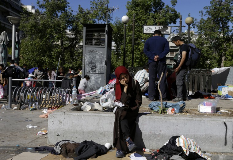 A girl sits as other migrants pack their belongings at Victoria square, where hundreds migrants and refugees stay temporarily before trying to continue their trip to more prosperous northern European countries, in Athens on Thursday, Oct. 1, 2015. Authorities in Greece have reopened a disused Galatsi Olympic Hall as police escorted buses carrying about 500 people, mostly from Syria and Afghanistan. (AP Photo/Thanassis Stavrakis)