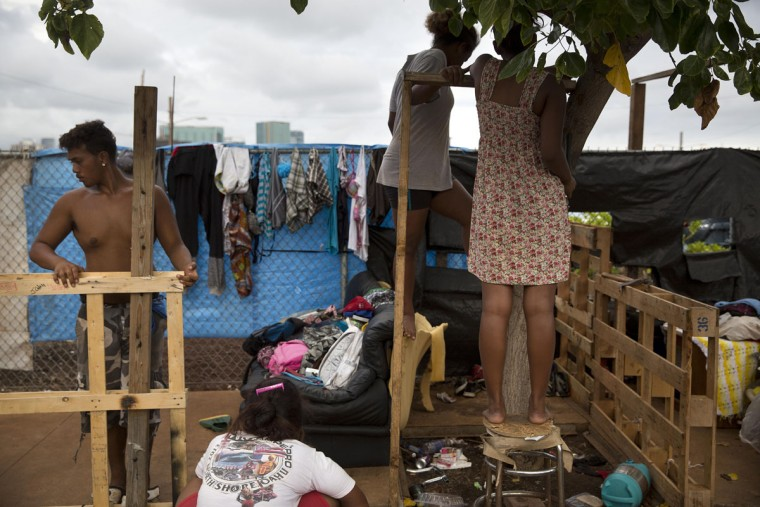 18-year-old Roy Kalama, left, gets help from friends as he tries to build a makeshift tent using pallets at a homeless encampment in the Kakaako district of Honolulu. The camp, one of the nation's largest homeless encampment and once home to hundreds of people, was recently cleared by Hawaii officials. (AP Photo/Jae C. Hong)