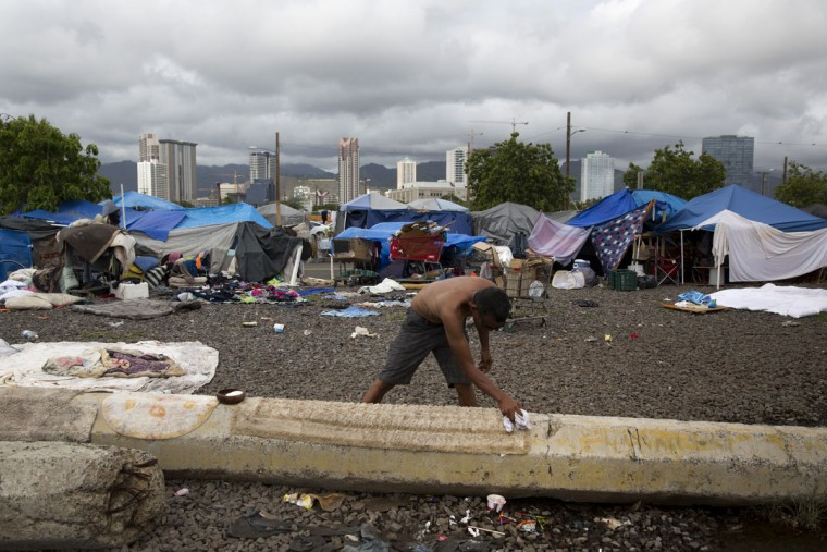 A homeless man washes an old area rug at a homeless encampment in the Kakaako district of Honolulu. The number of homeless people in Hawaii grew over the past five years, and the state's population of unsheltered families ballooned 46 percent from 2014 to 2015, said Scott Morishige, state coordinator on homelessness. (AP Photo/Jae C. Hong)