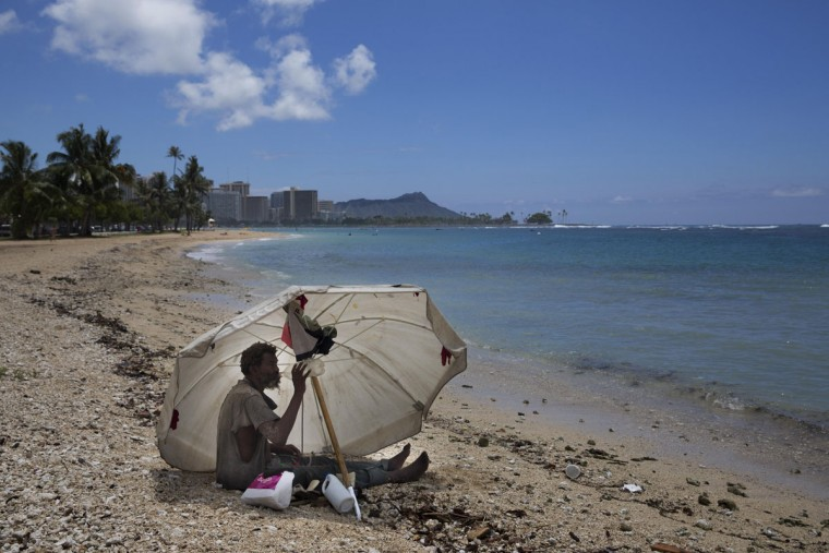 A homeless man drinks water while sitting on the beach at Ala Moana Beach Park located near Waikiki in Honolulu. Homelessness in Hawaii has grown steadily in recent years, leaving the state with the nation's highest rate of homeless people per capita. (AP Photo/Jae C. Hong)