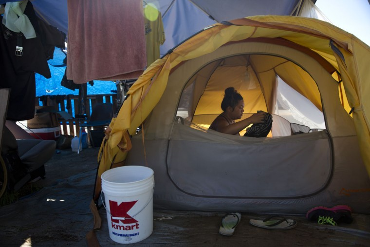 Deja-Lynn Rombawa-Quarles, a 24-year-old woman who works part time at an elementary school as a group leader, sits in her tent at a homeless encampment in the Kakaako district of Honolulu. Rombawa-Quarles is one of a growing number of working poor in Honolulu who, through a combination of high housing costs, a dearth of affordable housing and bad circumstances, wound up living on the street. (AP Photo/Jae C. Hong)