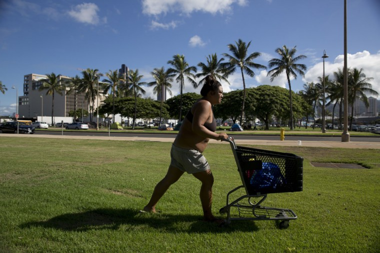 Deja-Lynn Rombawa-Quarles, a 24-year-old homeless woman who works part time at an elementary school as a group leader, pushes her cart to do laundry at a homeless encampment in the Kakaako district of Honolulu. Rombawa-Quarles is one of a growing number of working poor in Honolulu who, through a combination of high housing costs, a dearth of affordable housing and bad circumstances, wound up living on the street. (AP Photo/Jae C. Hong)