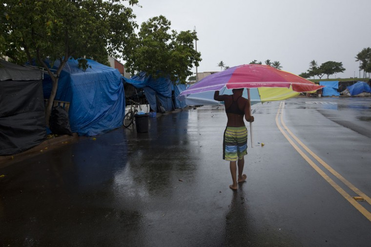 A girl uses a large umbrella to take cover from the rain while walking through a homeless encampment in the Kakaako district of Honolulu. The encampment, which included 180 tents and more than 300 people, swelled after the City of Honolulu started banning sitting and lying down on sidewalks in 2014. (AP Photo/Jae C. Hong)