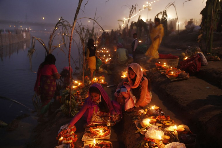 Indian Hindu devotees perform rituals at sunset on the banks of the Yamuna River during the Chhath Puja festival in New Delhi, India, Tuesday, Nov. 17, 2015. During Chhath, an ancient Hindu festival, rituals are performed to thank the Sun god for sustaining life on earth. (AP Photo /Tsering Topgyal)