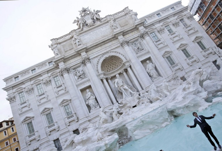 "Fendi CEO Pietro Beccari poses for the photographers as he pretends to fall into the newly restored Trevi Fountain during the official inauguration in Rome, Tuesday, Nov. 3, 2015. The historical fountain, famed as a setting for the film ""La Dolce Vita'' and the place where dreamers leave their coins, reopened after a 17-months restoration financed by the Fendi fashion house. (AP Photo/Gregorio Borgia)"