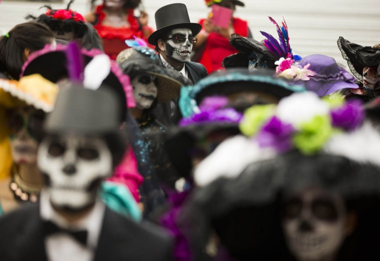 """People dressed as """"Catrinas"""" commemorate Day of the Dead, a holiday that honors the deceased, during a Catrina Fest in Mexico City, Saturday, Oct. 31 2015. The figure of a skeleton wearing an elegant broad-brimmed hat was first done as a satirical engraving by artist Jose Guadalupe Posada sometime between 1910 and his death in 1913. (Esteban Felix/AP photo)"""