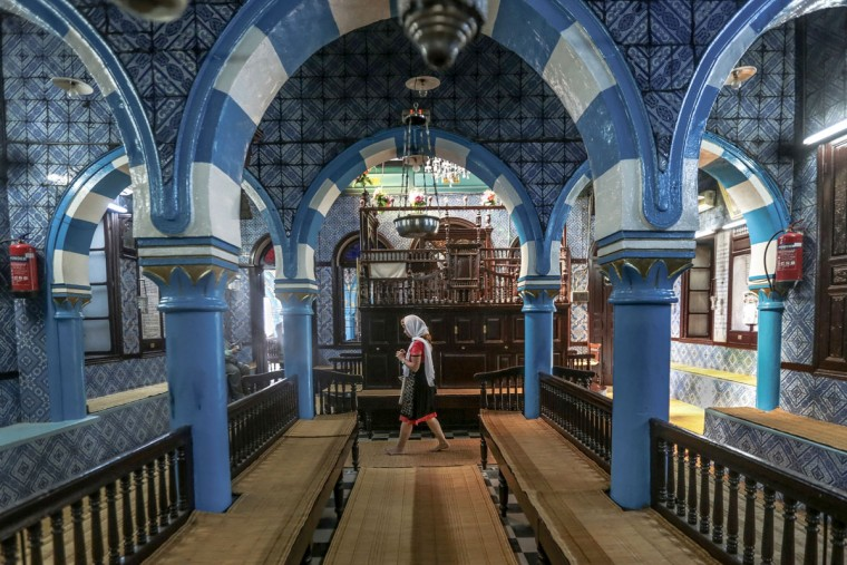 A tourist visits La Ghriba, the oldest synagogue in Africa, on the Island of Djerba, southern Tunisia. Beneath intricate tile walls bearing blue and yellow geometric shapes that would not seem out of place at a mosque. The synagogueís name can be translated as ìstrangeî or ìmiraculous.î (AP Photo/Mosa'ab Elshamy)