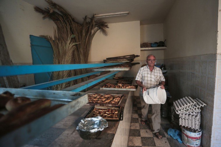 Yofel Sabbagh, 46, walks inside a bakery as he prepares Challah, a special Jewish bread, on the eve of Shabbath, at Hara Kbira, the main Jewish neighborhood on the Island of Djerba, southern Tunisia. The Jewish community in the resort island of Djerba traces its roots all the way back to Babylonian exile of 586 B.C., and is one of the few communities of its kind to have survived the turmoil around the creation of Israel, when more than 800,000 Jews across the Arab world either emigrated or were driven from their homes. (AP Photo/Mosa'ab Elshamy)