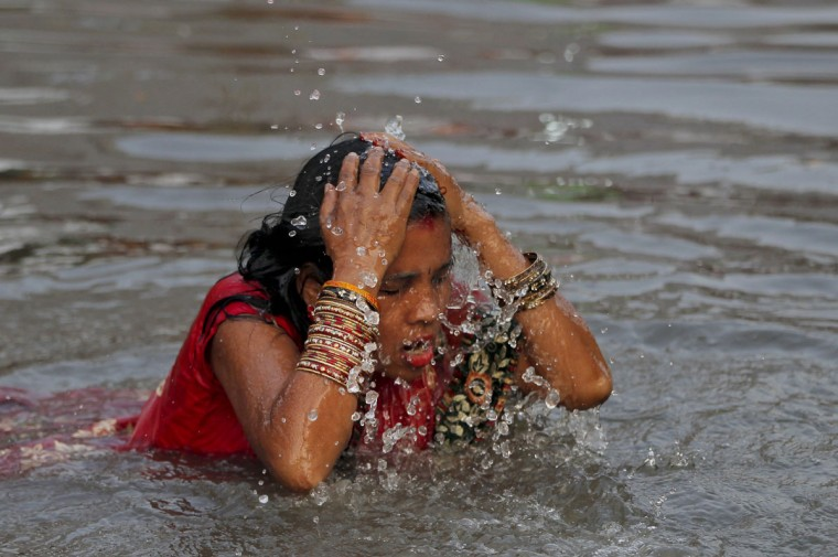 A Nepalese woman takes a holy dip in the Bagmati River before offering prayers during the Chhath Puja festival in in Kathmandu, Nepal, Tuesday, Nov. 17, 2015. On Chhath, an ancient Hindu festival, rituals are performed to thank the Sun god for sustaining life on earth. (AP Photo/Niranjan Shrestha)