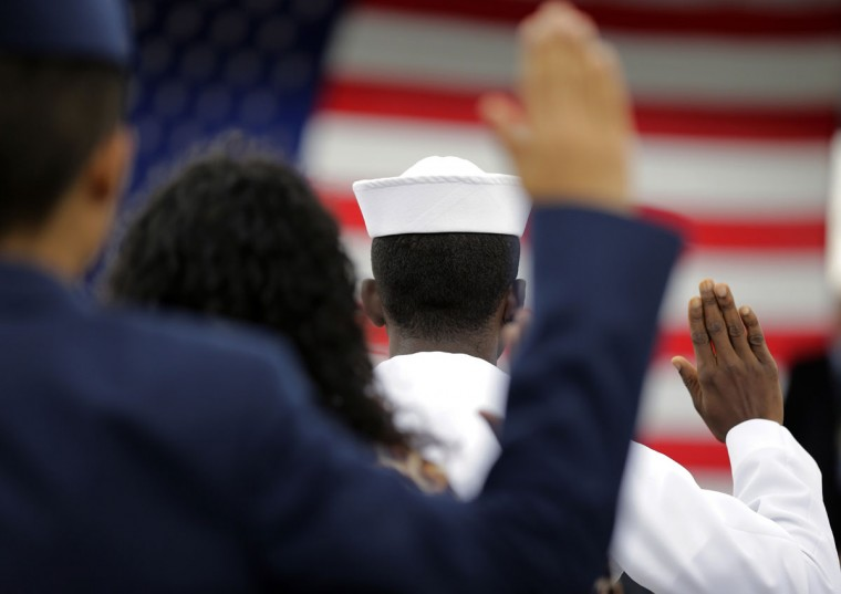 A group of current and former military personnel take part in a Naturalization ceremony during a Veteran's Day observance at Fort Sam Houston National Cemetery, Wednesday, Nov. 11, 2015, in San Antonio. (AP Photo/Eric Gay)