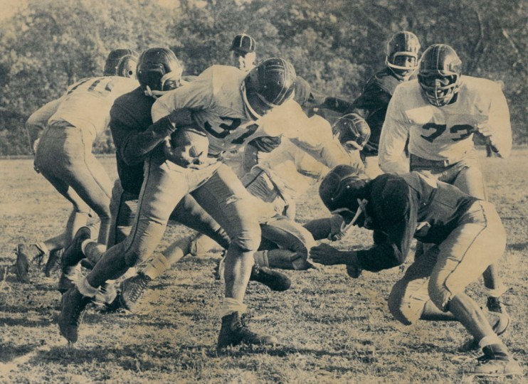 Edmondson fullback Milt Lane runs for first down in the second quarter as Southern's Erv Brice and Gary Woodlon close in from font and rear. (Ralph Dohme/Baltimore Sun, 1960)