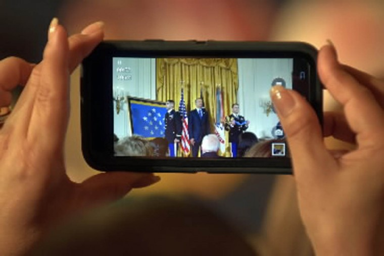 A member of the audience takes pictures of the ceremony. In the White House East Room, President Barack Obama presents Captain Florent A. Groberg, U.S. Army (Ret), the Medal of Honor for conspicuous gallantry for his courageous actions while serving as a Personal Security Detachment Commander for Task Force Mountain Warrior, 4th Infantry Brigade Combat Team, 4th Infantry Division during combat operations in Asadabad, Kunar Province, Afghanistan on August 8, 2012. He is the tenth living recipient to be awarded the Medal of Honor for actions in Afghanistan. (Algerina Perna, Baltimore Sun)