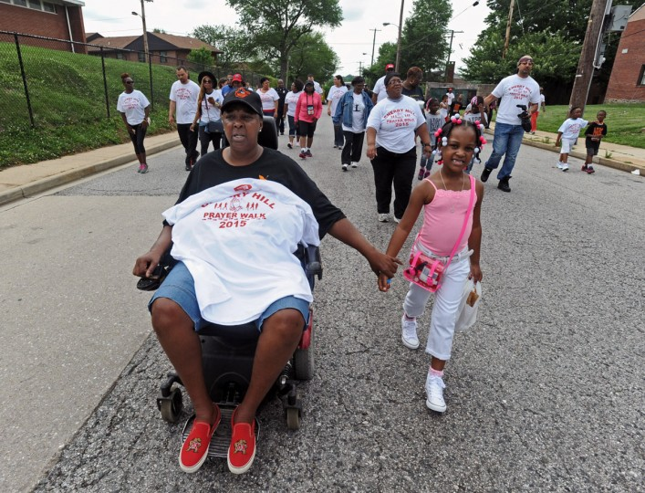 Aniyah Bomar, 6, walks with grandmother Elva Gilmore and about 150 other Cherry Hill residents and supporters in the Fourth annual Cherry Hill Prayer Walk organized by Michael Battle on June 6, 2015. (Kenneth K. Lam/Baltimore Sun)