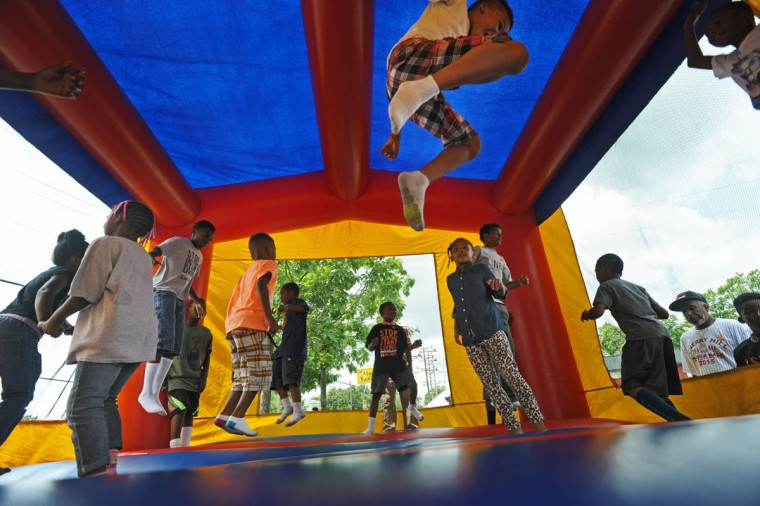 Children from the Cherry Hill neighborhood play in a moon bounce game during block party after the Fourth annual Cherry Hill Prayer Walk organized by Michael Battle on June 6, 2015. (Kenneth K. Lam/Baltimore Sun)