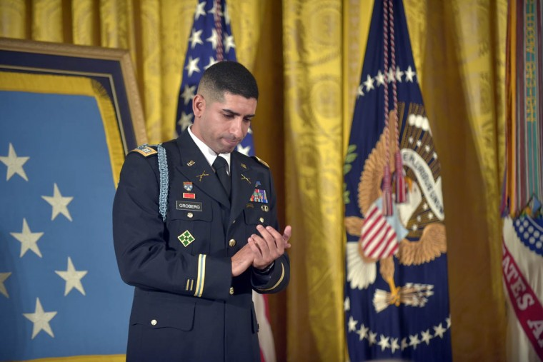 As President Barack Obama speaks of Florent's comrades in arms, Captain Florent A. Groberg, U.S. Army (Ret) applauds their service. In the White House East Room, President Barack Obama presents Captain Florent A. Groberg, U.S. Army (Ret), the Medal of Honor for conspicuous gallantry for his courageous actions while serving as a Personal Security Detachment Commander for Task Force Mountain Warrior, 4th Infantry Brigade Combat Team, 4th Infantry Division during combat operations in Asadabad, Kunar Province, Afghanistan on August 8, 2012. He is the tenth living recipient to be awarded the Medal of Honor for actions in Afghanistan. (Algerina Perna, Baltimore Sun)