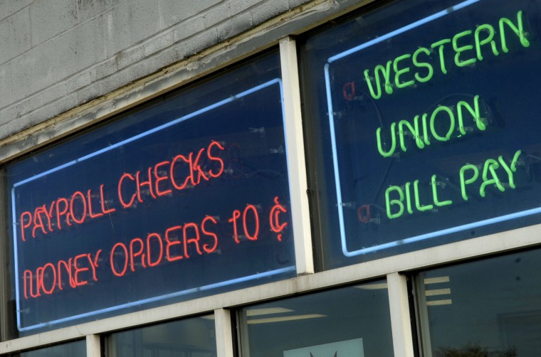 Neon signs are pictured in the window of AA State check cashing and income tax store on Hanover Street in Cherry Hill on Sept. 19, 2007. (Baltimore Sun photo by Amy Davis)