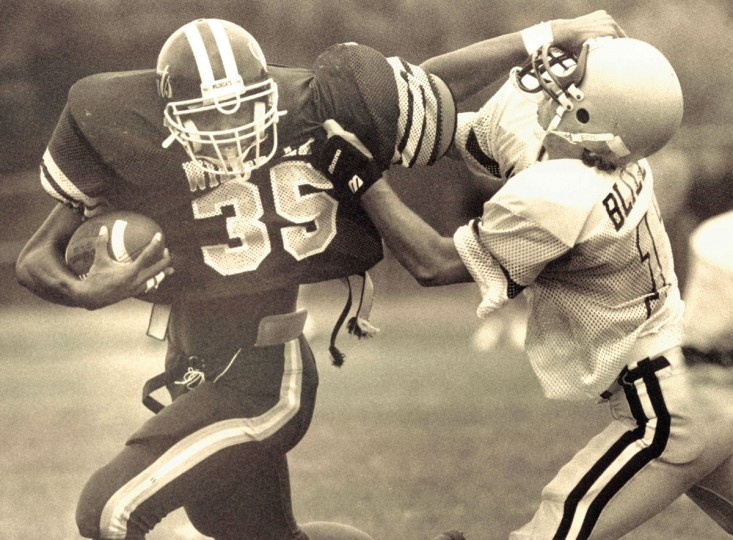 Mike Green of the Wilde Lake High School Wildcats hooks his thumb inot the helmet of Sotuh Carroll High School defender Brad Blizzard. (Jason Lee/Baltimore Sun, 1992)
