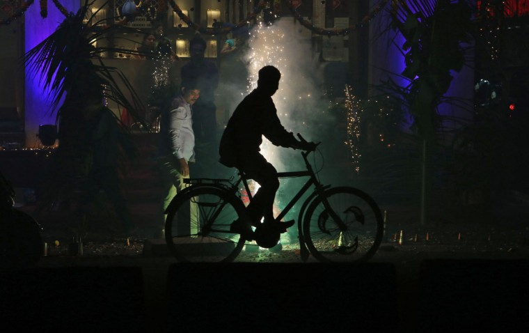 An Indian man rides past people playing with firecrackers during Diwali celebrations in Hyderabad, India, Wednesday, Nov. 11, 2015. Diwali, the festival of lights, is one of Hinduism's most important festivals dedicated to the worship of Lakshmi, the Hindu goddess of wealth. (AP Photo/Mahesh Kumar A.)