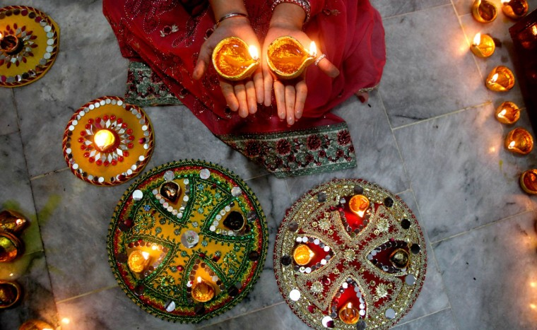A Pakistani Hindu woman lights candles during Diwali celebrations at a local temple in Lahore, Pakistan, Wednesday, Nov. 11, 2015. Diwali, the festival of lights, is one of Hinduism's most important festivals dedicated to the worship of Lakshmi, the Hindu goddess of wealth. (AP Photo/K.M. Chaudary)