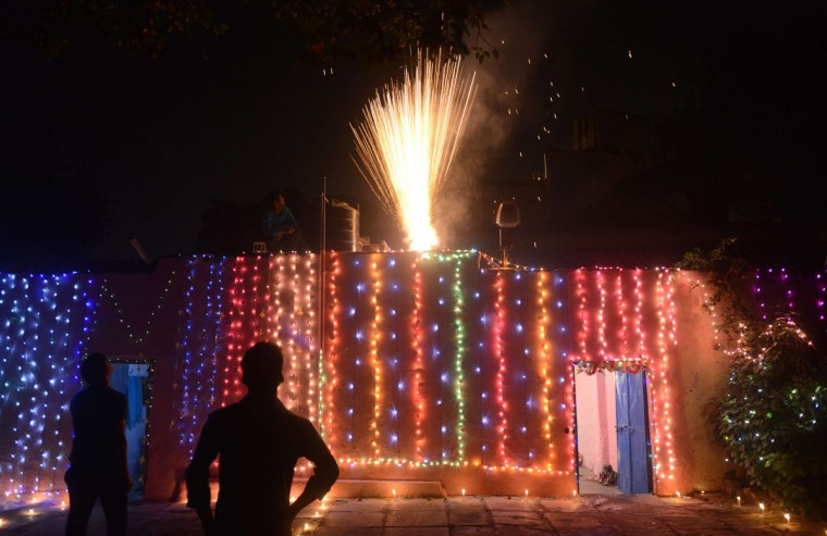 Indian residents watch fireworks outside their homes to celebrate Diwali, the Festival of Lights, in Allahabad on November 11, 2015. (Sanjay Kanojia/AFP/Getty Images)