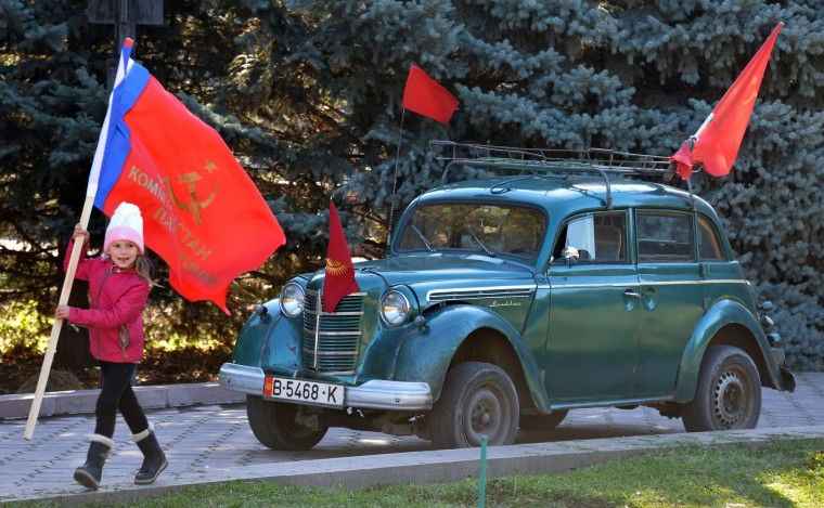 "A girl holds a red flag in front of Soviet car ""Moscvich"" during a rally to mark the 98th anniversary of Russia's Bolshevik Revolution in central Bishkek on November 7, 2015. (Vyacheslav Oseledko/AFP-Getty Images)"