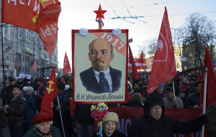 Russian Communists hold red flags and a portrait of Soviet state founder Vladimir Lenin as they gather for a demonstration to mark the 98th anniversary of the Bolshevik revolution in Moscow, Russia, Saturday, Nov. 7, 2015. For decades Nov. 7 used to be a holiday celebrating the 1917 Bolshevik Revolution and which is no longer a public holiday in Russia. (AP Photo/Ivan Sekretarev)