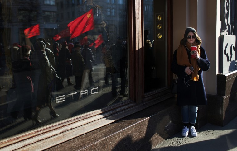 A woman drinks coffee while watching a Communists demonstration marking the 98th anniversary of the Bolshevik revolution in Moscow, Russia, Saturday, Nov. 7, 2015. For decades Nov. 7 used to be a holiday celebrating the 1917 Bolshevik Revolution and which is no longer a public holiday in Russia. (AP Photo/Ivan Sekretarev)