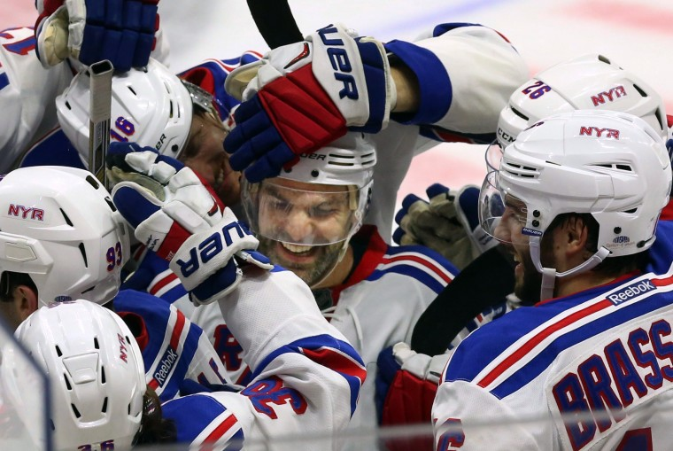New York Rangers' Dan Boyle, center, celebrates his shoot-out goal with teammates during overtime NHL hockey action against the Ottawa Senators, in Ottawa, on Saturday, Nov. 14, 2015. The Rangers beat the Senators 2-1. (Fred Chartrand/The Canadian Press via AP)