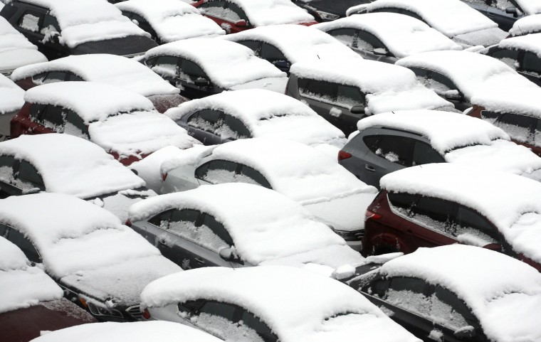 Cars are covered by snow in rental car parking lot at O'Hare International Airport, Saturday, Nov. 21, 2015, in Chicago. The first significant snowstorm of the season blanketed some parts of the Midwest with more than a foot of snow and more was on the way Saturday, creating hazardous travel conditions and flight delays. (AP Photo/Nam Y. Huh)
