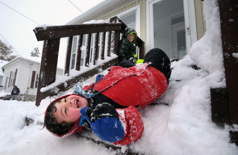 Luca Damato slides down packed snow on his stairs as Adam Stankus looks on while they play outside in Kenosha, Wis., Saturday, Nov. 21, 2015. The first significant snowstorm of the season blanketed some parts of the Midwest with more than a foot of snow and more was on the way Saturday, creating hazardous travel conditions and flight delays. (Sean Krajacic/The Kenosha News via AP)