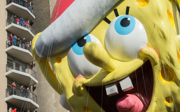 Spectators watch as the balloon of Spongebob Squarepants is moved down Central Park West during the Macy's Thanksgiving Day Parade, Thursday, Nov. 26, 2015 in New York. (AP Photo/Bryan R. Smith)