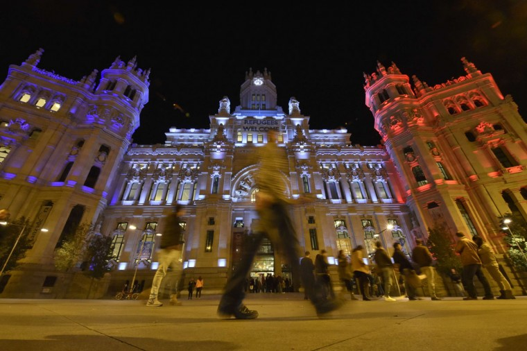 People cross the street past the Cibeles Palace facade, Madrid's town hall, illuminated red, white and blue to represent the French national standard in Madrid on November 14, 2015. (GERARD JULIEN/AFP/Getty Images)