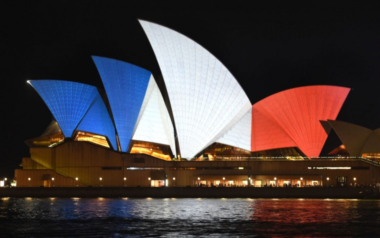 The iconic sails of the Sydney Opera House are lit in red, white and blue, resembling the colors of the French flag, in Sydney on November 14, 2015, as Australians express their solidarity with France following a spate of coordinated attacks that left 128 dead and 180 injured in Paris late on November 13. (WILLIAM WEST/AFP/Getty Images)