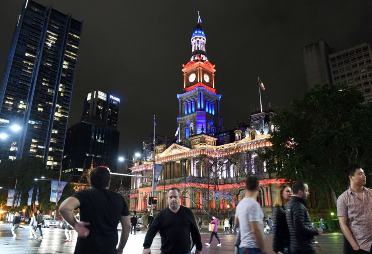 People walk past the Sydney Town Hall as it is lit in red, white and blue, resembling the colors of the French flag, in Sydney on November 14, 2015, as Australians express their solidarity with France following a spate of coordinated attacks that left 128 dead and 180 injured in Paris late on November 13. (WILLIAM WEST/AFP/Getty Images)