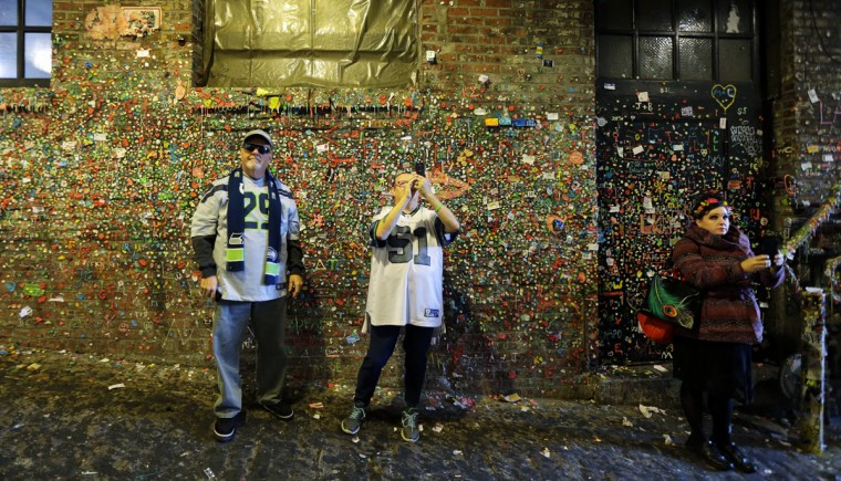Richard and Wendy Thorsnes, of Tacoma, Wash., photograph Seattle's famous gum wall at Pike Place Market, Monday, Nov. 9, 2015. (AP Photo/Ted S. Warren)