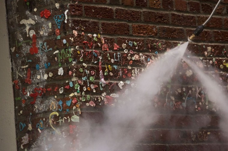 A worker uses a pressure steamer to remove 20-years worth of chewing gum that is being removed in Post Alley at the Pike Place Market in Seattle, Washington on November 11, 2015. (JASON REDMOND/AFP/Getty Images)