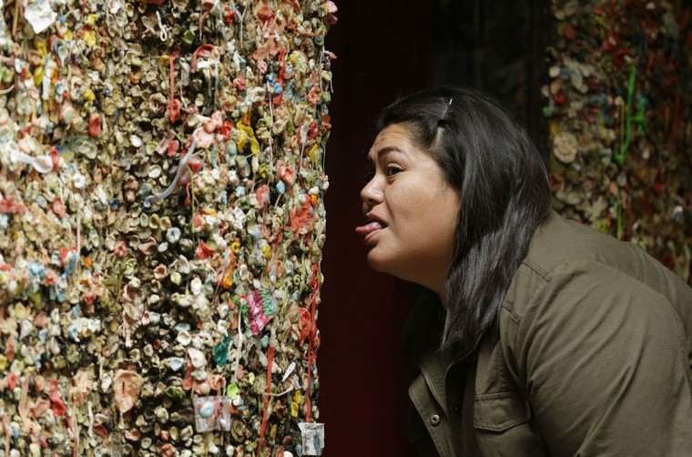 Louise Kaiwi, who was visiting Seattle from Hawaii, pretends to lick a wall full of gum as she poses for a photo taken by a friend at Seattle's famous gum wall at Pike Place Market, Monday, Nov. 9, 2015. (AP Photo/Ted S. Warren)