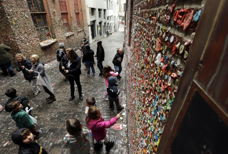 "Visitors check out Seattle's ""gum wall"" at Pike Place Market, Monday, Nov. 9, 2015. Known as the ""gum wall,"" the sticky landmark has become a popular attraction to visitors and locals. (AP Photo/Ted S. Warren)"